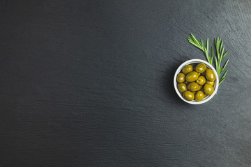 Set of green olives on plate and rosemary on a black stone background