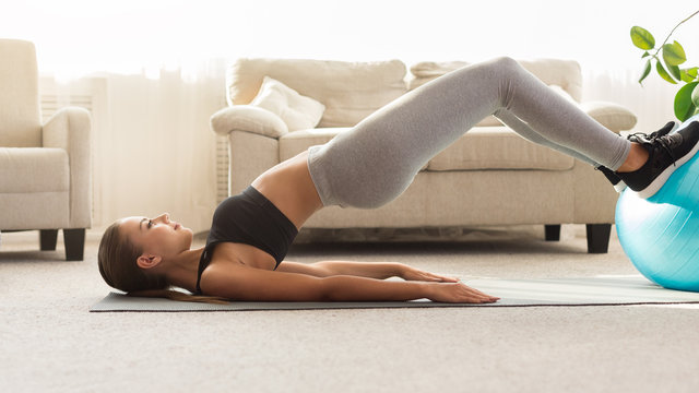 Side view of woman doing half bridge pose with fitball