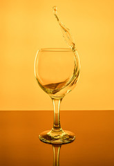 Splash of wine in a glass. Drink in glass on a yeallow background.