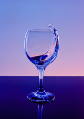 Splash of wine in a glass. Drink in glass on a blue background.