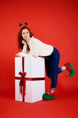 Woman with a big christmas present looking at copy space