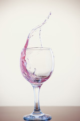 Splash of wine in a glass. Pink drink in glass on a white background.