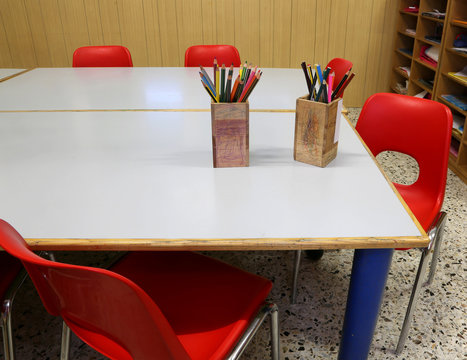 classroom of a school with red chairs and pencils
