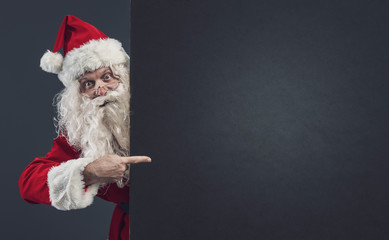 Happy Santa pointing at a blank sign