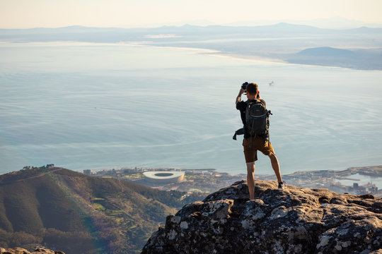A man is taking a picture on top of the table mountain