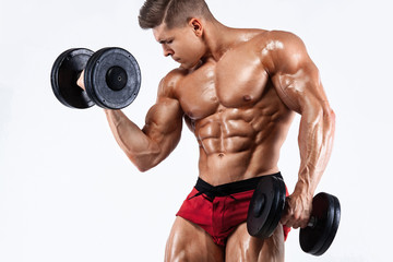 Brutal strong muscular bodybuilder athletic man pumping up muscles with dumbbell on white background. Workout bodybuilding concept.