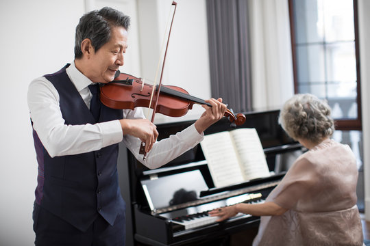 Noble senior couple playing the piano and violin