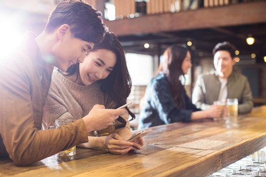 Happy friends using smartphone in bar