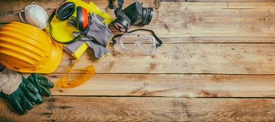 Construction safety. Protective hard hat, headphones, gloves and glasses on wooden background, banner Wall mural