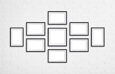 Frames collage, nine black wooden frameworks on white bricks wall
