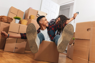 Young couple having fun and riding in cardboard boxes at new home.