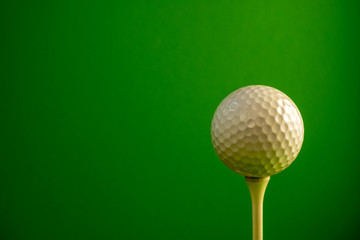 Close-up of a golf ball on a tee. Green background. Copy space.
