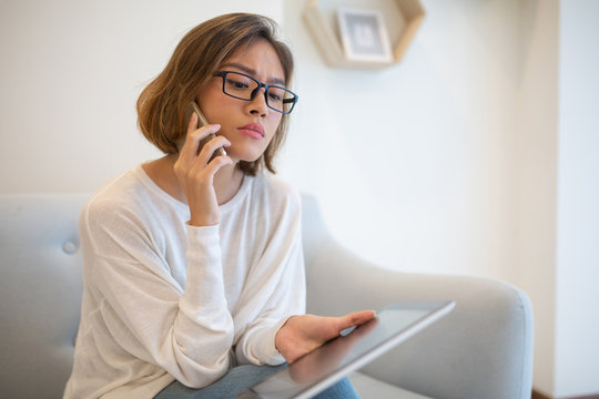 Focused woman holding tablet and talking on phone on sofa. Pretty young Asian lady sitting and using digital devices at home. Technology and communication concept.