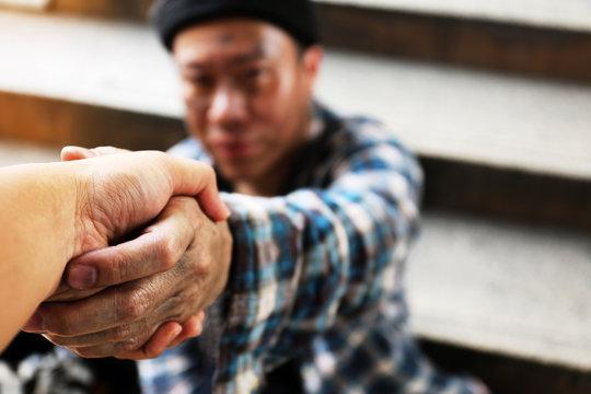 Handshake homeless man on walkway street in the city.