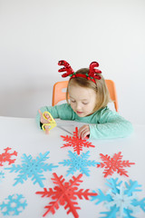 The  girl at a table with horns of a deer cuts out snowflakes at a table. Preparation for a holiday