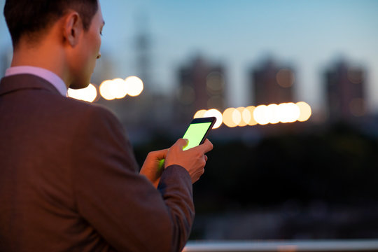 Confident young businessman using smart phone