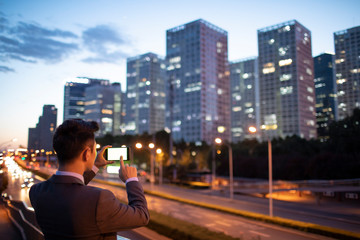 Young businessman taking photos with smart phone