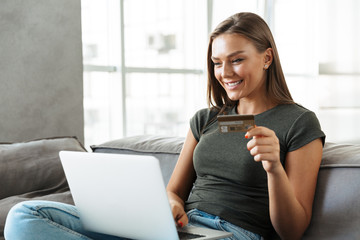 Smiling young woman sitting on a couch at home