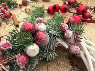 Florist workplace. Christmas wreath of twigs with pine needles. Decorated Christmas wreath on wood background.