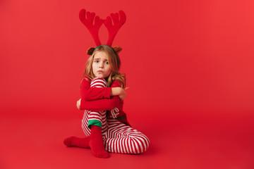 Upset little girl wearing Christmas raindeer costume