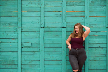 blond girl model plus size on the background of a green wall
