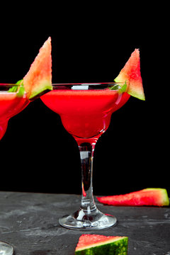 Watermelon margarita cocktail on black background. Fresh watermelon lemonade