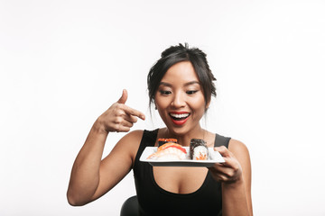 Beautiful young asian woman holding plate with sushi set