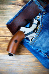 silver revolver nagant with brown handle in the pocket