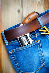 old silver revolver and vintage blue jeans