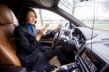 middle-aged woman with a smartphone in car