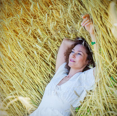 beautiful woman lies among the ears of corn in the field