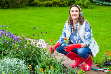smiling woman in kerchief and red boots planting flowers