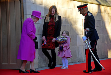 Evie Hayden, aged 4, and her mother Michelle, present Britain's Queen Elizabeth with a bouquet of flowers at the end of a visit to The Honourable Society of Lincoln's Inn in London