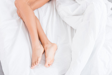 low section of young woman laying in bed during morning time at home