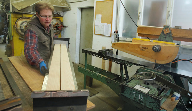 A worker places heated wood into a frame before shaping it, at Swiss sled manufacturer 3R AG in Sulgen