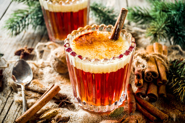 Winter holidays traditional drink, homemade hot buttered rum with spices, over old rustic wooden background with christmas tree branches, copy space