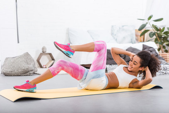 smiling african american sportswoman doing abs on fitness mat in bedroom at home