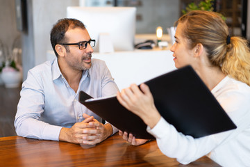 Confident female manager showing her project to male executive. Mid adult businessman wearing glasses having meeting with young partner or colleague. Planning concept