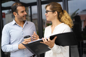Portrait of cheerful business colleagues talking at coffee break. Mid adult bearded man holding coffee cup communicating to young woman wearing glasses with folder indoors. Colleagues concept