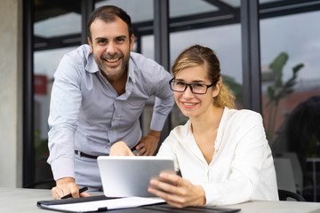 Portrait of happy business colleagues with digital tablet looking at camera and smiling. Young Caucasian woman wearing glasses sitting at table and mid adult man standing by. Team concept