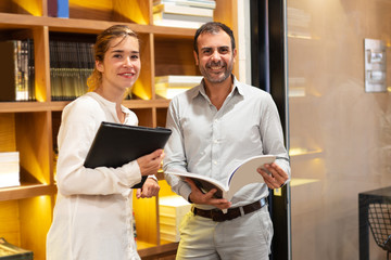 Portrait of happy businesswoman and male client with catalogue. Young Caucasian woman with folder and mid adult man holding magazine smiling in office. Business relationship concept