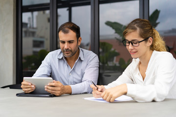 Portrait of male and female colleagues working in office. Mid adult Caucasian man using digital tablet and young woman working with papers together at one table. Corporate concept