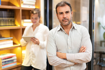 Portrait of serious male leader standing with folded arms. Mid adult Caucasian businessman looking at camera with confident expression, female colleague standing behind. Leadership concept