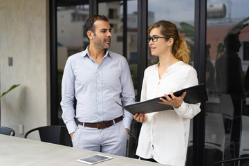 Portrait of smiling woman showing project to her executive in papers. Caucasian businessman and businesswoman talking in boardroom. Planning concept