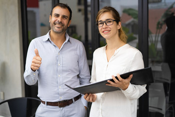 Portrait of successful team of young woman and mid adult man. Businessman smiling and showing thumbs up, woman wearing glasses holding folder. Success concept