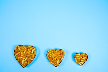 Heart shaped of gold pills on blue paper background.