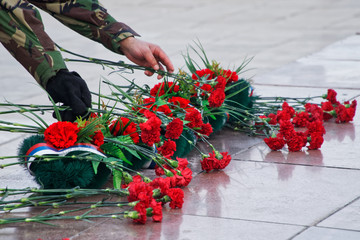 Flowers and a wreath in memory of those killed in wars and armed conflicts. The memory of the victims of the war