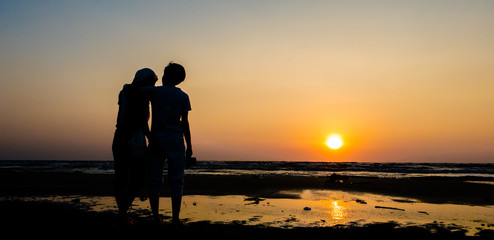 Asian of couple Lesbian romantic hugging on the beach Sunset background Summer honeymoon vacation and holidays shoot photo by smart phone