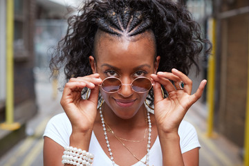 Young black woman with sunglasses looks to camera, portrait