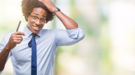 Afro american man holding credit card over isolated background stressed with hand on head, shocked with shame and surprise face, angry and frustrated. Fear and upset for mistake.